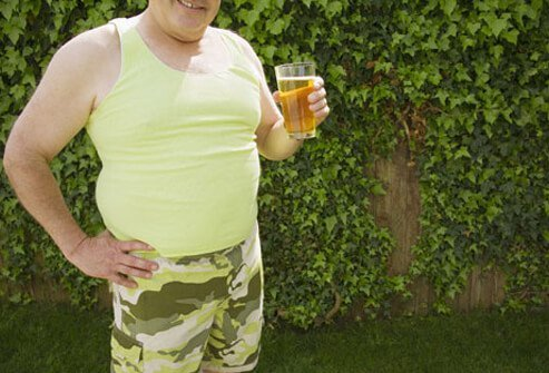 Photo of a man drinking beer in his backyard.