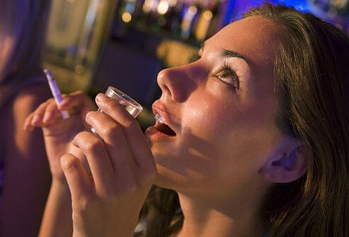 A drunken woman holds a cigarette and a shot glass.