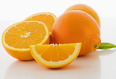 Whole and cut oranges, close-up.