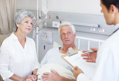 A doctor explains cancer treatment options to a couple in the hospital.