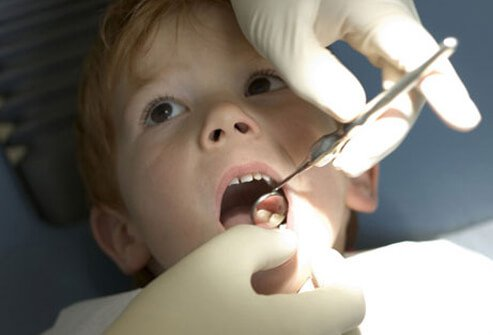 A dentist examining a boy's teeth for signs of celiac disease.