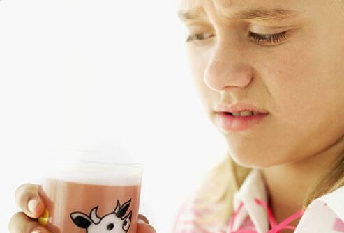 A repulsed girl with glass of chocolate milk.