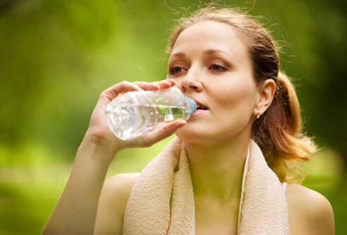 A woman drinks a bottle of water.