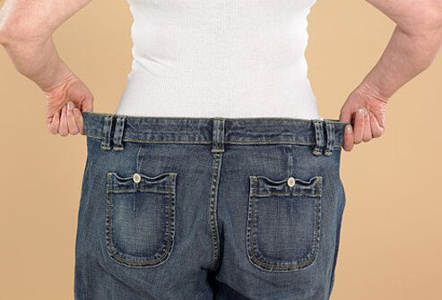 A woman's pants are loose due to weight loss.