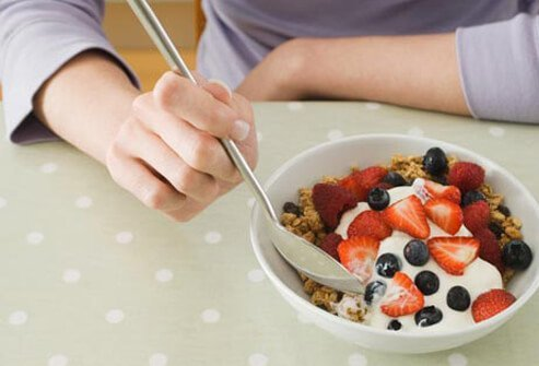 Photo of woman eating cereal after cervical cancer treatments.