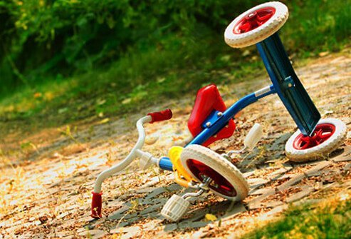 Photo of an upturned tricycle on the ground.