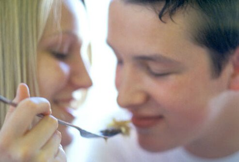 A woman feeds a man with a fork.
