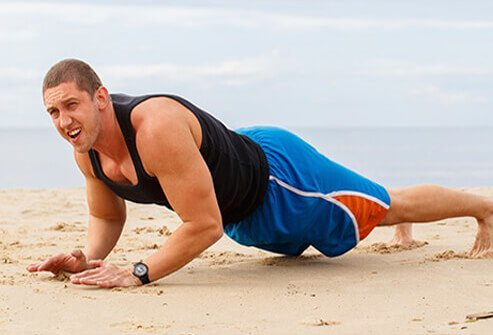 A man in pain after doing a push up.