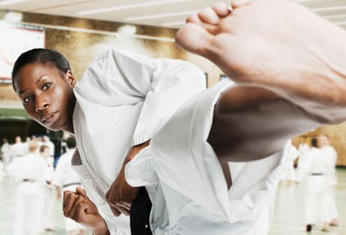 Photo of a woman doing a karate kick.
