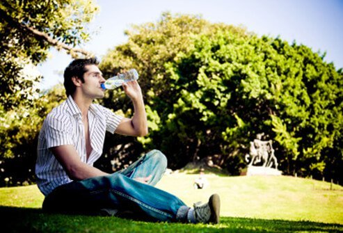 A man cools off in the shade while drinking bottled water.