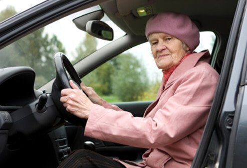 A senior woman preparing to drive her car.