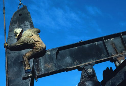 Photo of a man working on an oil pump.