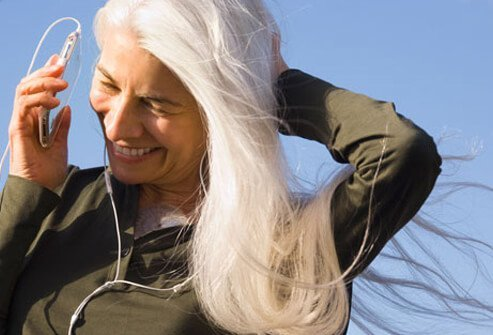 Photo of an older, happy woman listening to music.