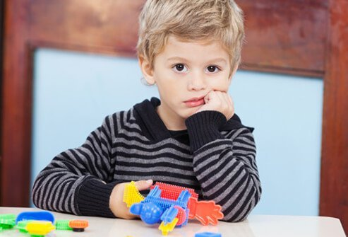 A sad and depressed preschool boy playing with toys.