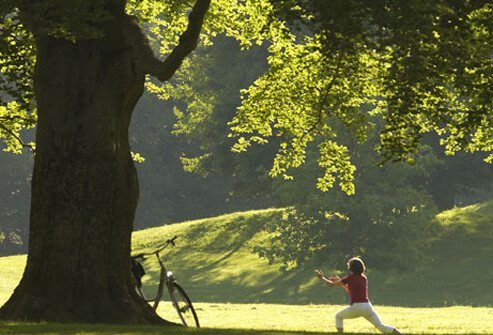 A woman does yoga under a tree.