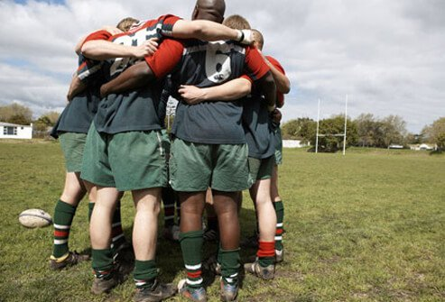 Rugby players form a huddle.