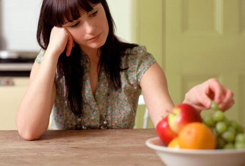 A depressed woman picks at fruit in a bowl.