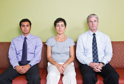 Three very absorbed adults sit next to each other.