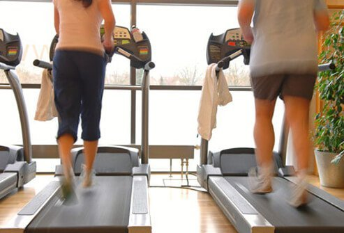 A couple jogging on the treadmill.