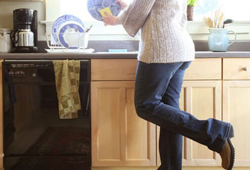 A woman doing dishes while balancing on one leg.