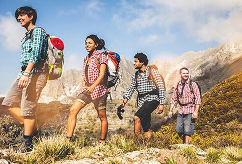 A group of young people with diabetes backpacking through the mountains.
