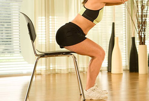 A Trainer using a chair to perform squat.