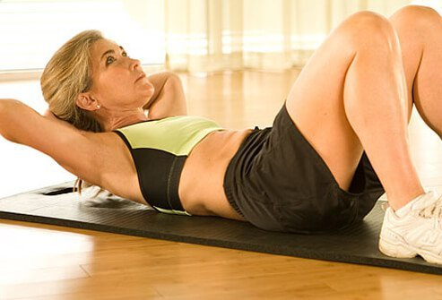A trainer demonstrating the proper form for crunches.