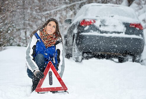 A woman is stranded in a snow storm.