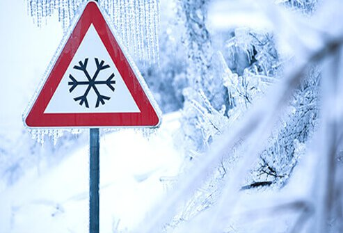 A winter-road-conditions sign covered in ice.