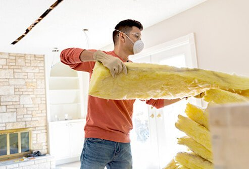 A man adds insulation to his home for winter.