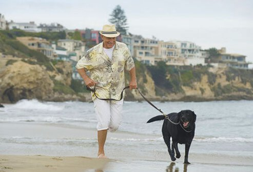 Photo of man and his dog at the beach, reducing his risk of erectile dysfunction.