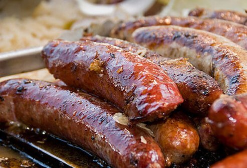Sausages being cooked on a grill.