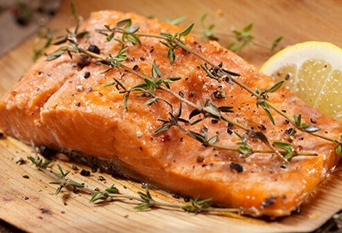 A cooked salmon fillet with herbs and lemon wedge, perfect to help fight depression.