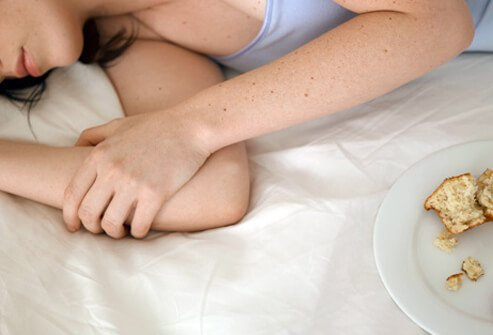 A woman asleep on her bed with a leftover plate of food.