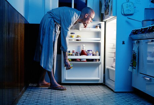 A man looking in refrigerator for a late night snack.