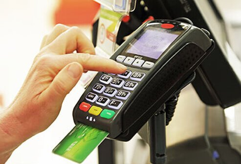 A person enters in a code on a credit card keypad.