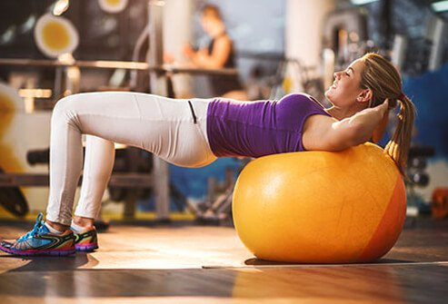 A woman at the gym uses a fitness ball.