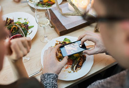 A man photographs his plate with a smart phone.