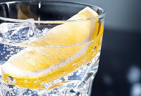 A fizzy drink garnished with a lemon.