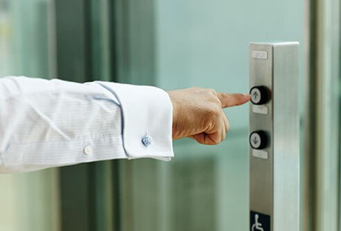 A man pushes the elevator buttons.