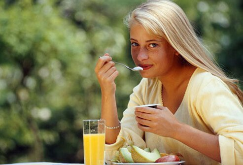 A young woman eats breakfast outdoors.