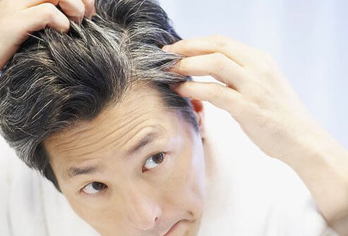 A man examines his gray hair in the mirror.
