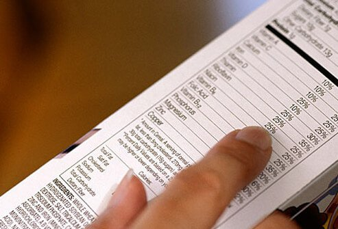 Photo of woman reading nutrition label.