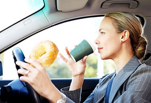 A woman driving her car eats a bagel for breakfast on the go.