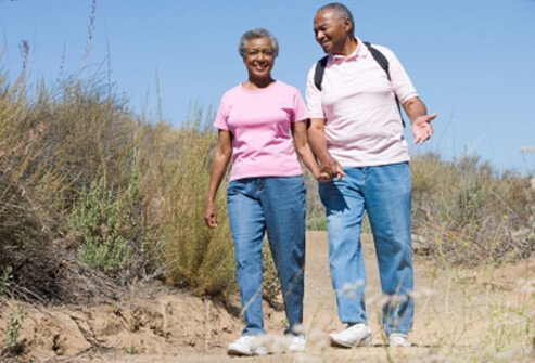A senior couple on a walk through the countryside.