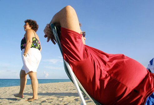 An overweight couple on beach, at risk for heart disease.