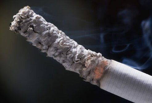 A close-up of cigarette with burning ash, a heart disease risk factor.