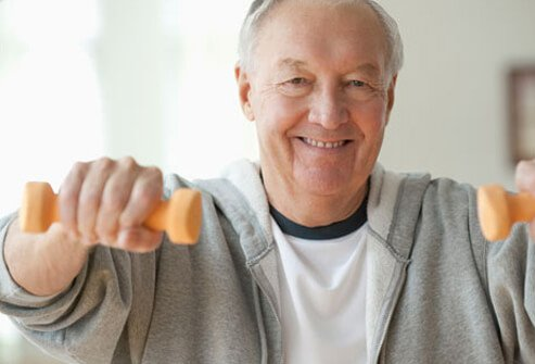 A senior man lifting weights, living healthy after a heart attack.