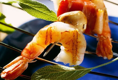 Shrimp on a skewer with bacon and mushrooms.