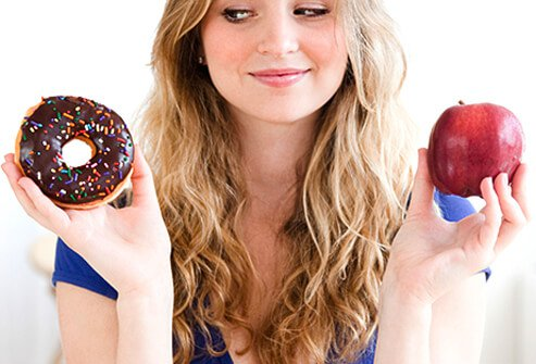 A woman tries to choose between a healthy and unhealthy meal.